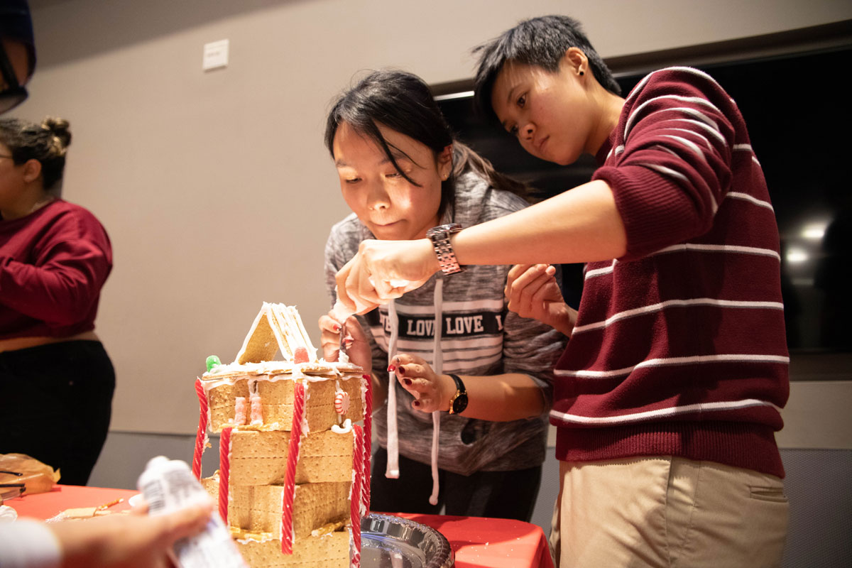 Two students building gingerbread house