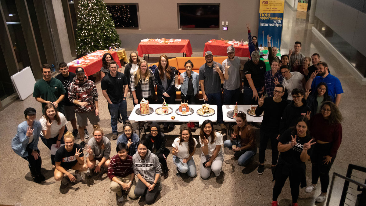 Group of about 40 students posing around gingerbread houses