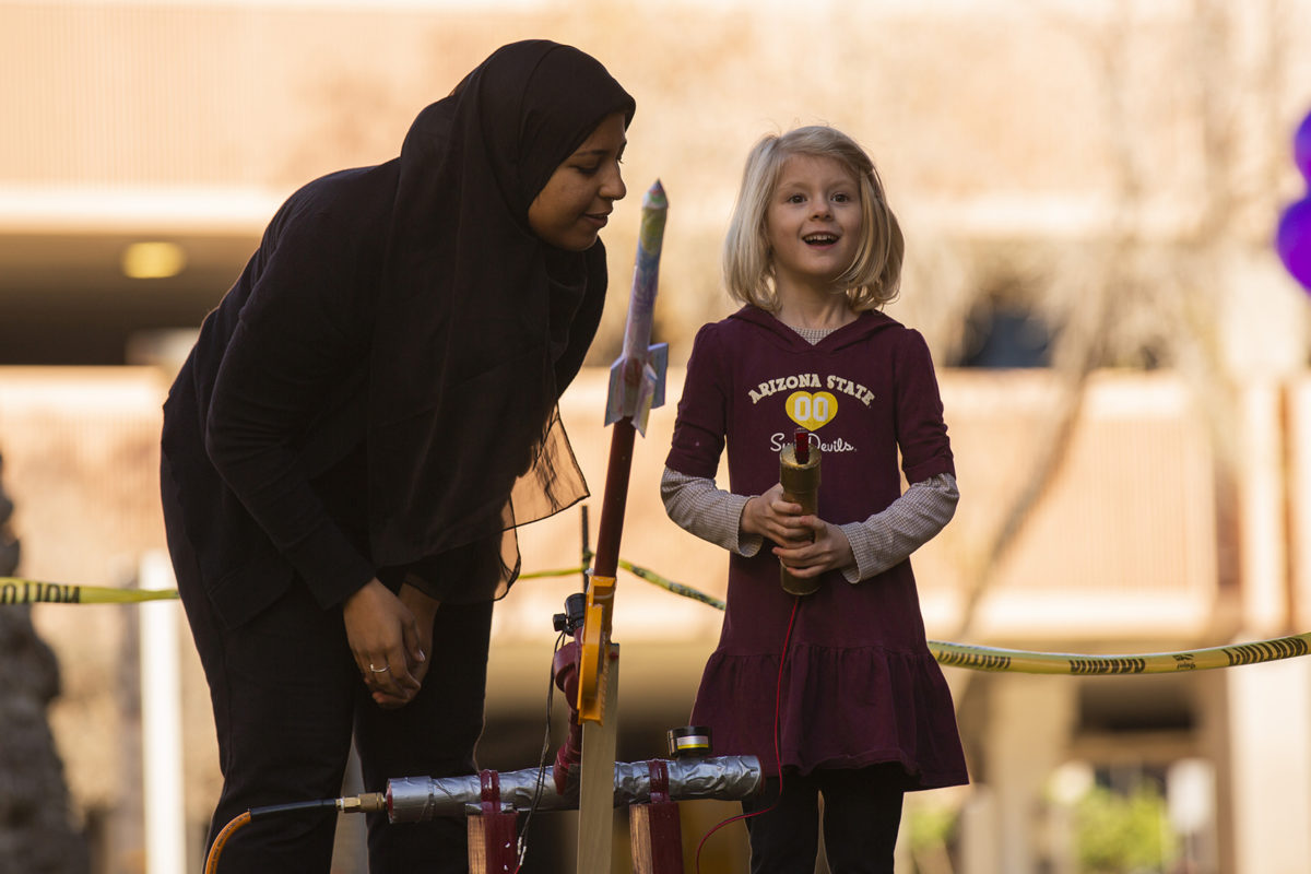 college student and younger girl standing by a paper rocket