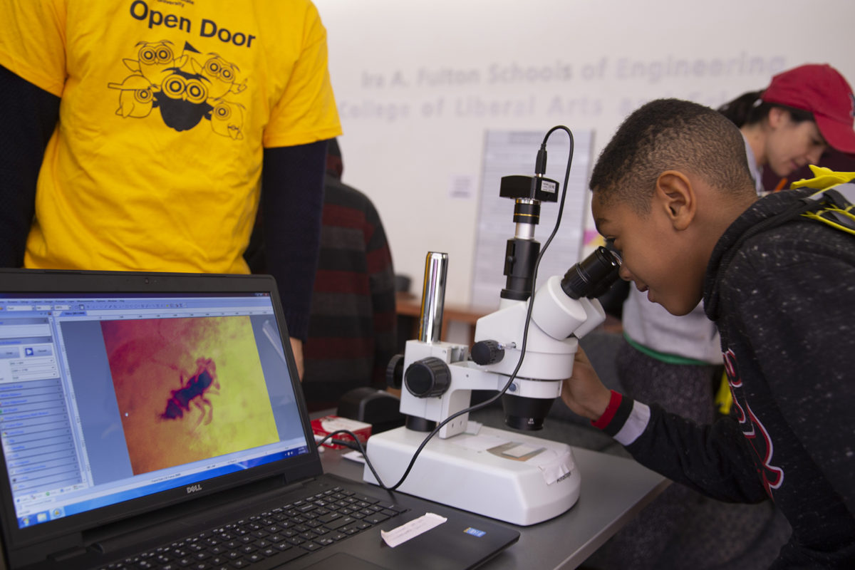 child looking into microscope