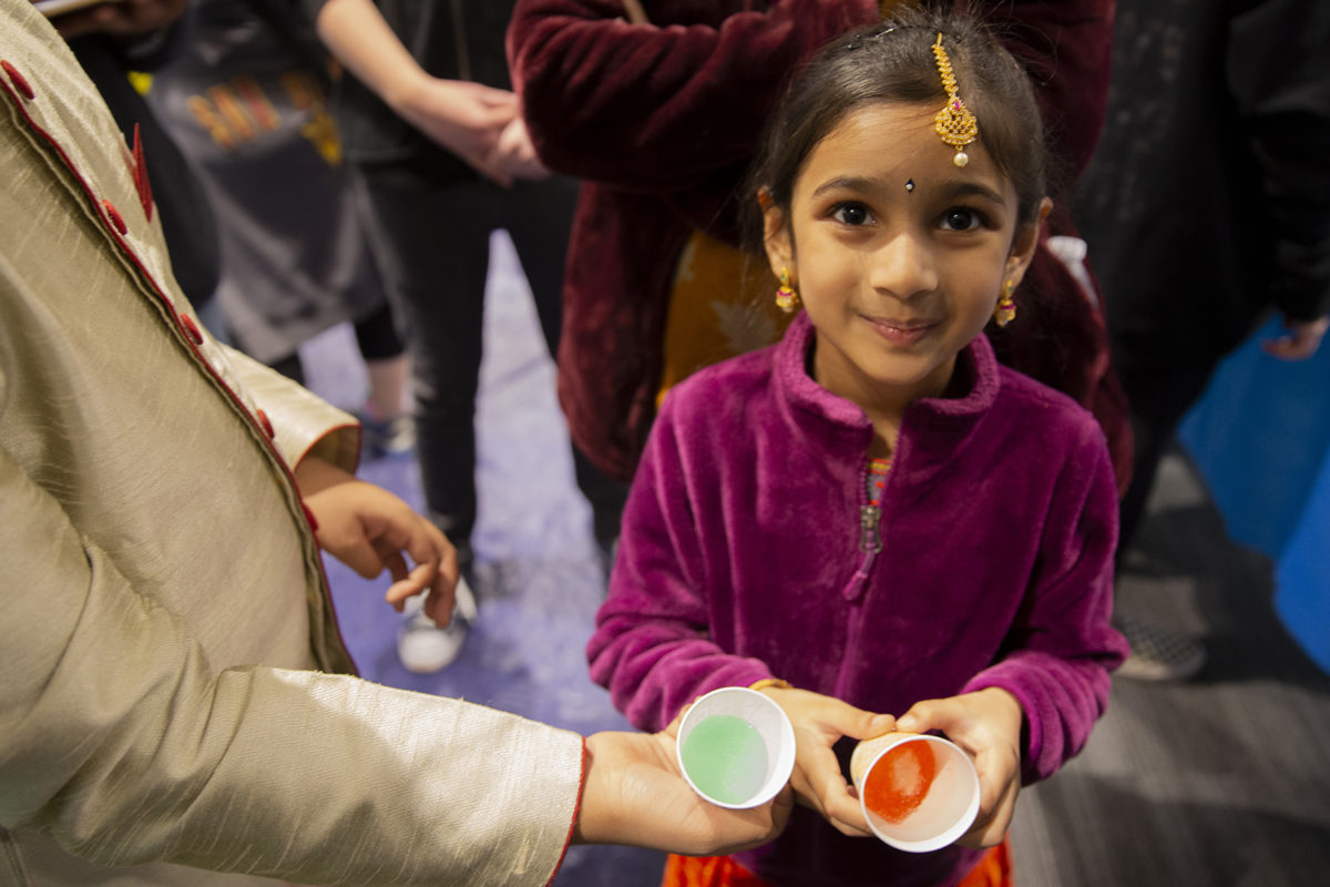 young girl holding a cup filled with colorful liquid