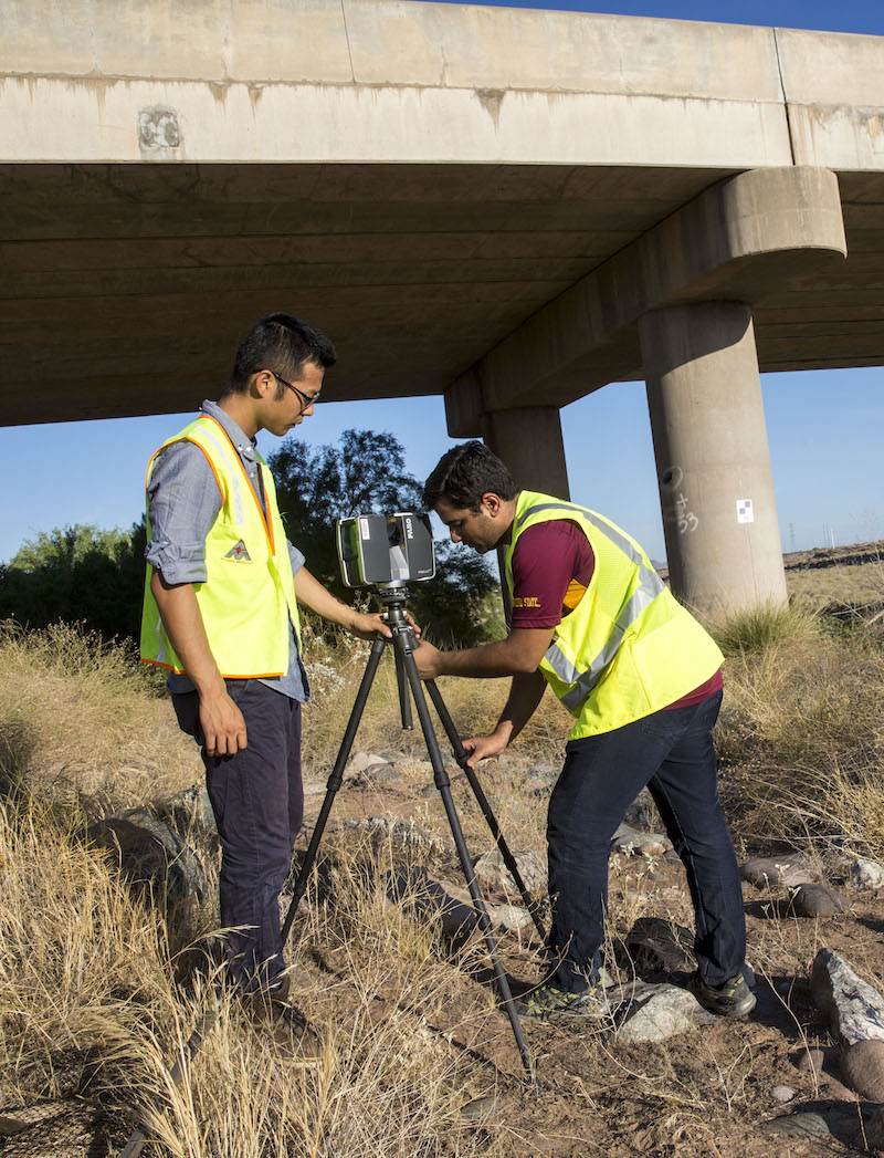 two people setting up surveying equipment underneathe an overpass