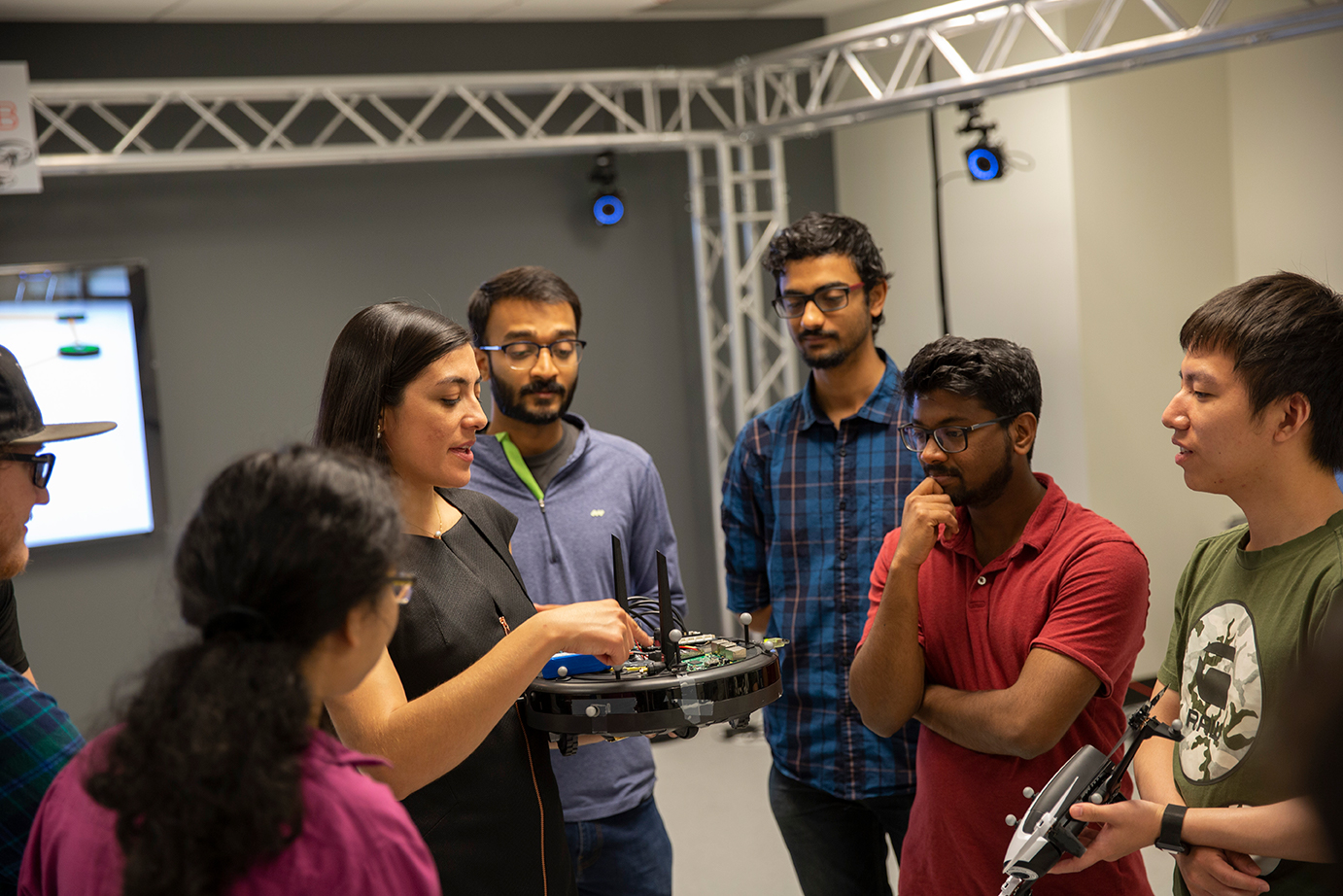 professor holding a robot, surrounded by students