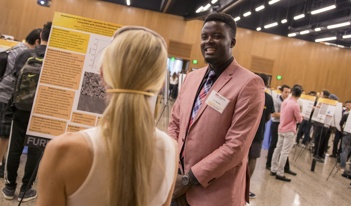Photo of student presenting research to someone at an event