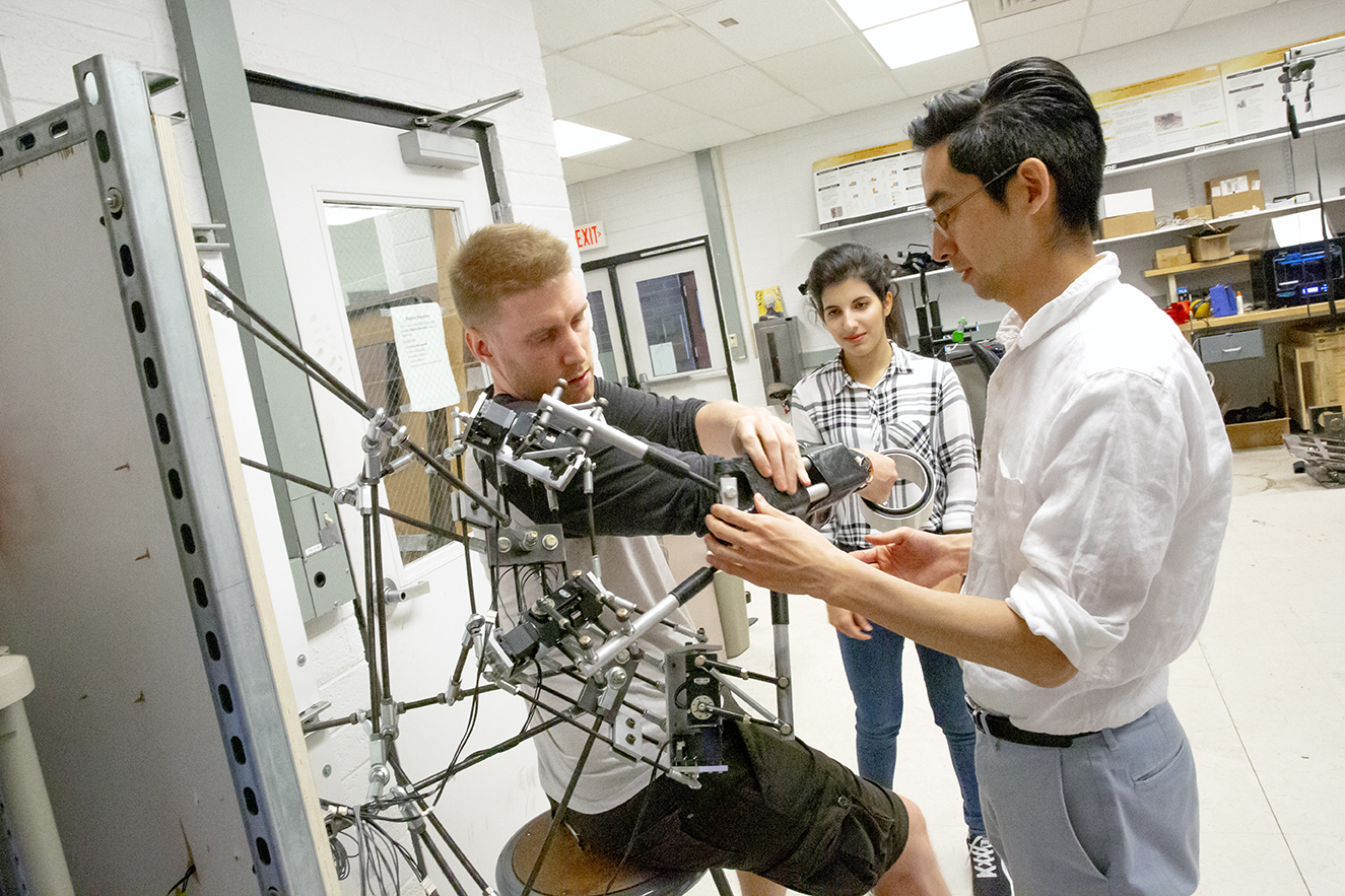 professor and student in a lab, student wearing a robotic device on his arm