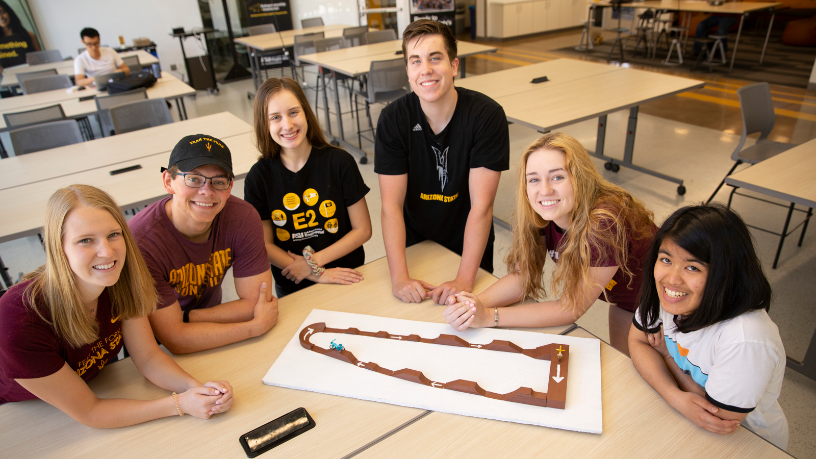 Six students sit at a table with a model bike trail path.