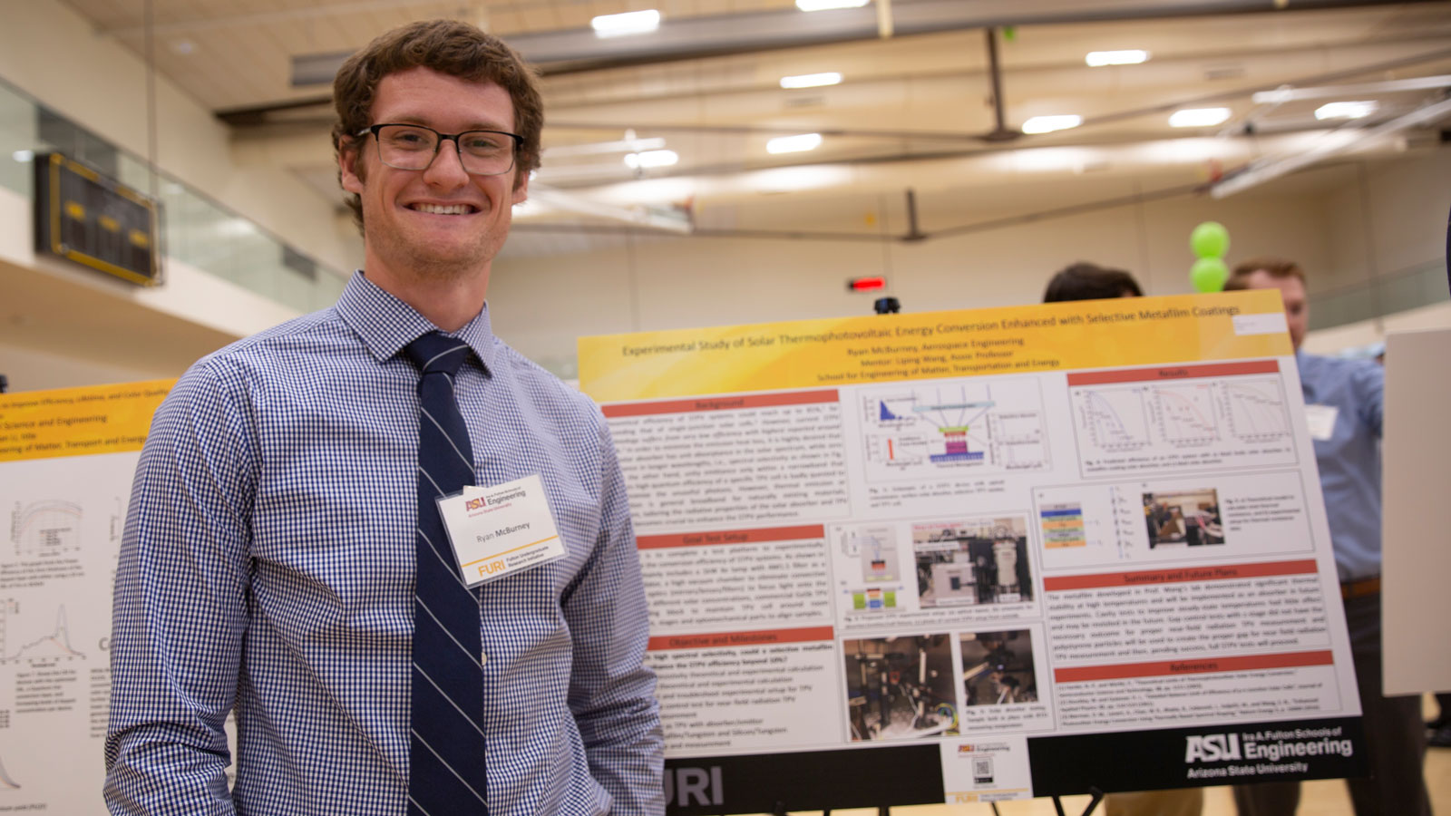 A student poses in front of a research poster.