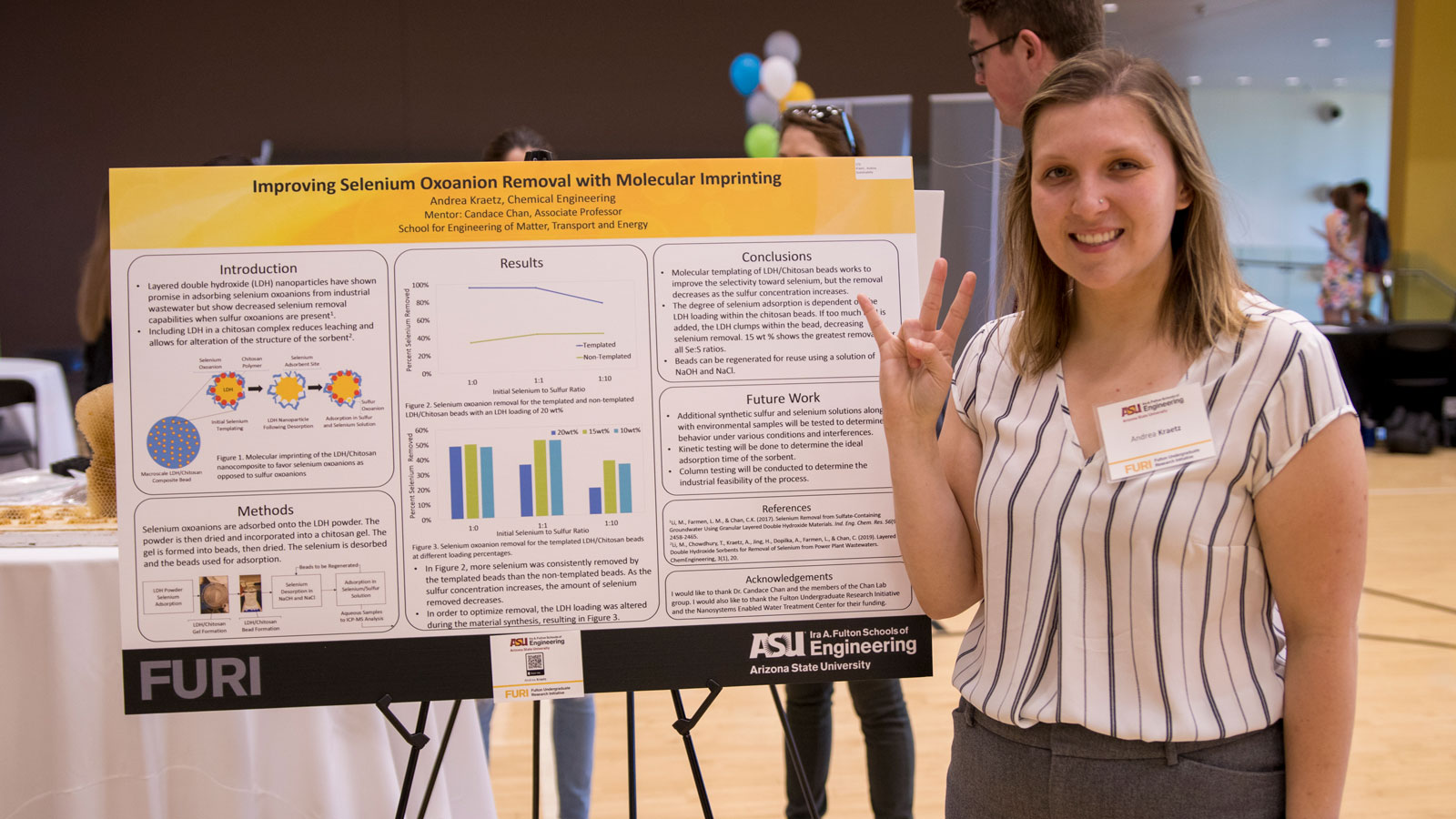 A student stands in front of a research poster.