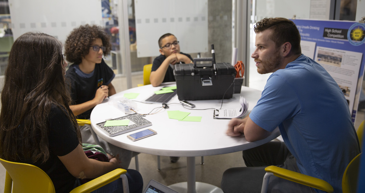 three high school students sitting talking to college student