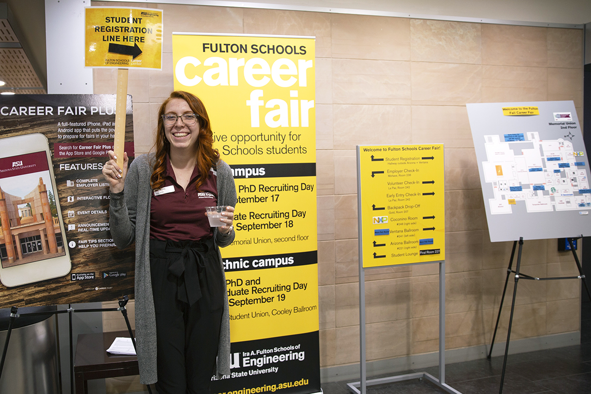 woman holding up a sign directing students where to go