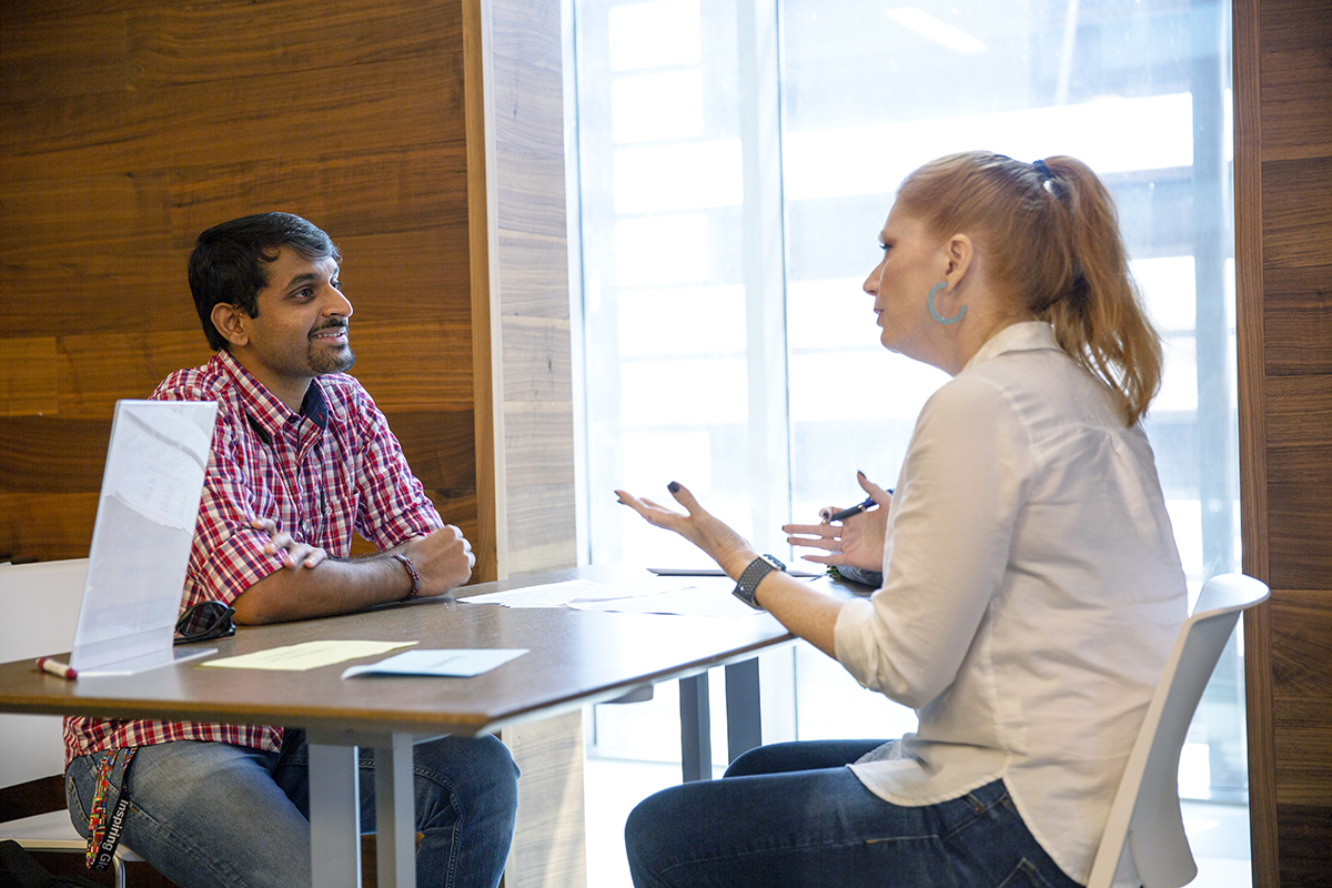 male student talking with woman at table
