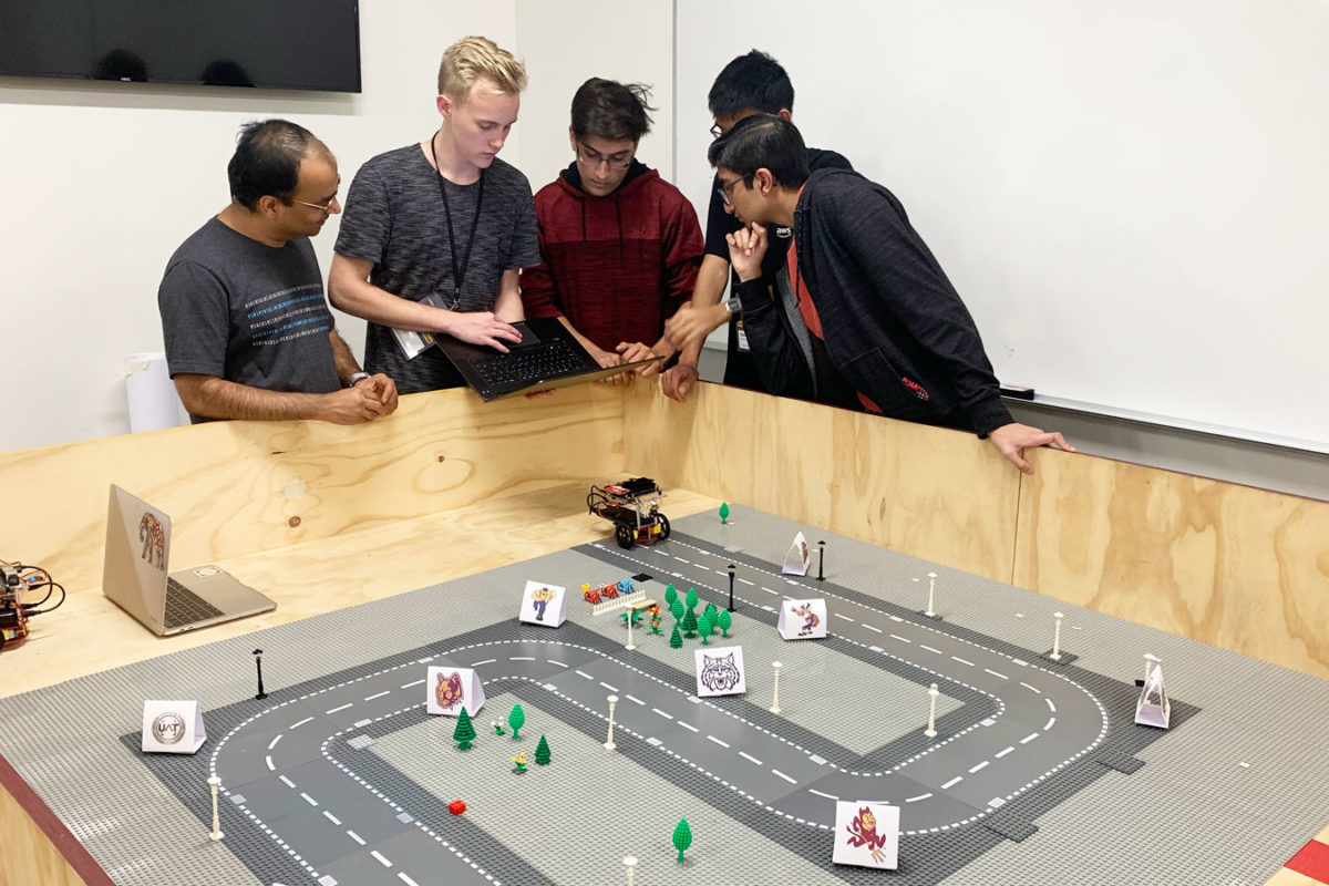 students behind a track for robots