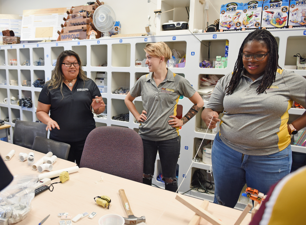 three students in a lab building a Rube Goldberg machine