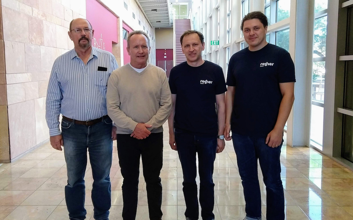Four men standing in a hallway