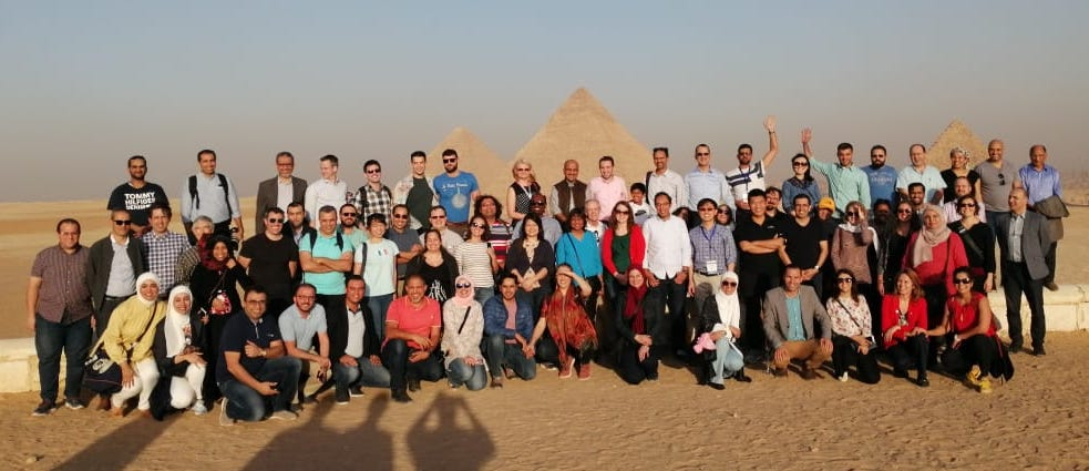 large group of people in front of the pyramids in Egypt