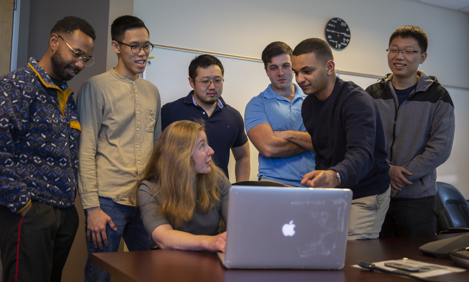 professor and students looking at a computer together
