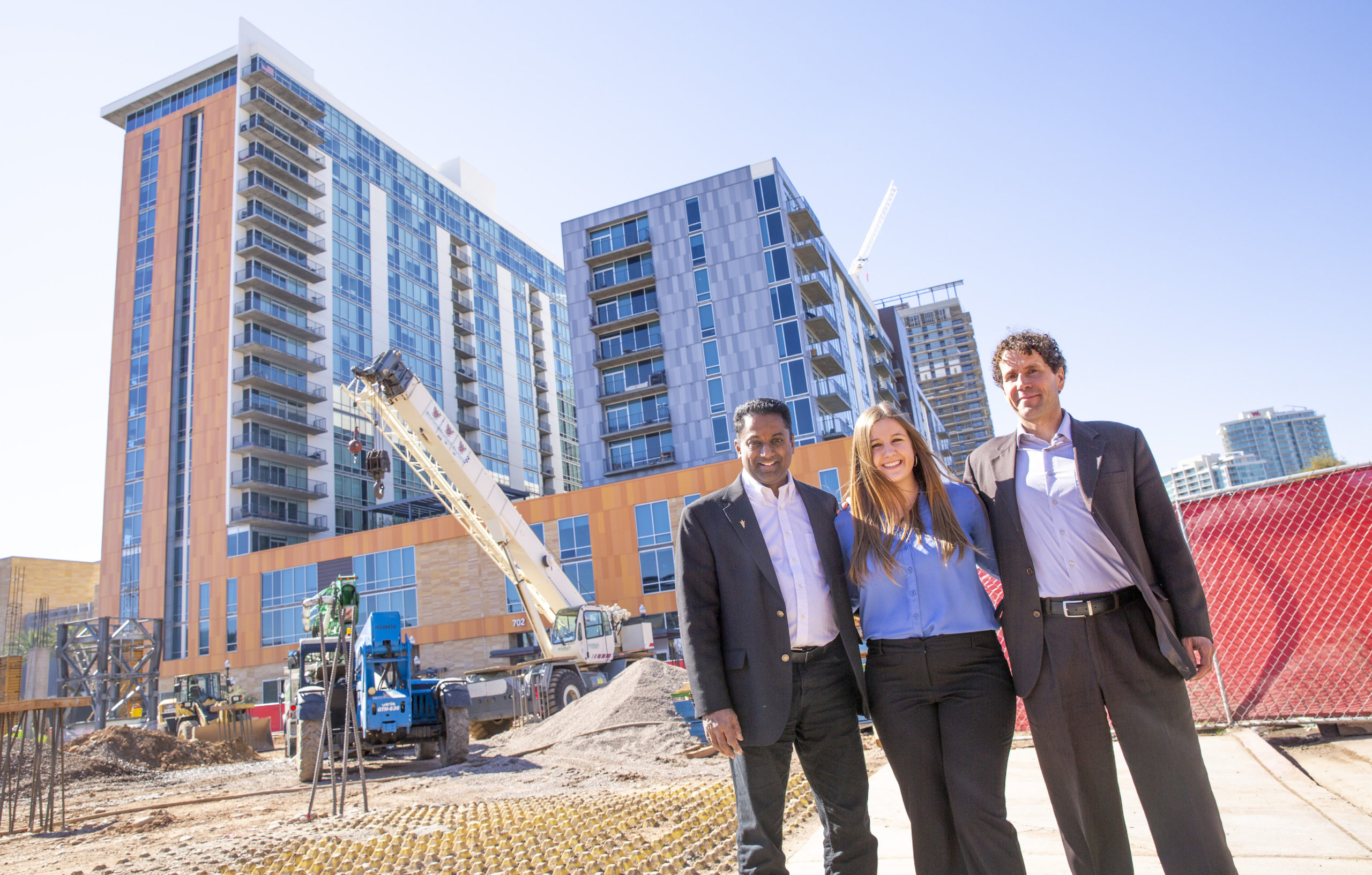 three people standing in front of a construction site