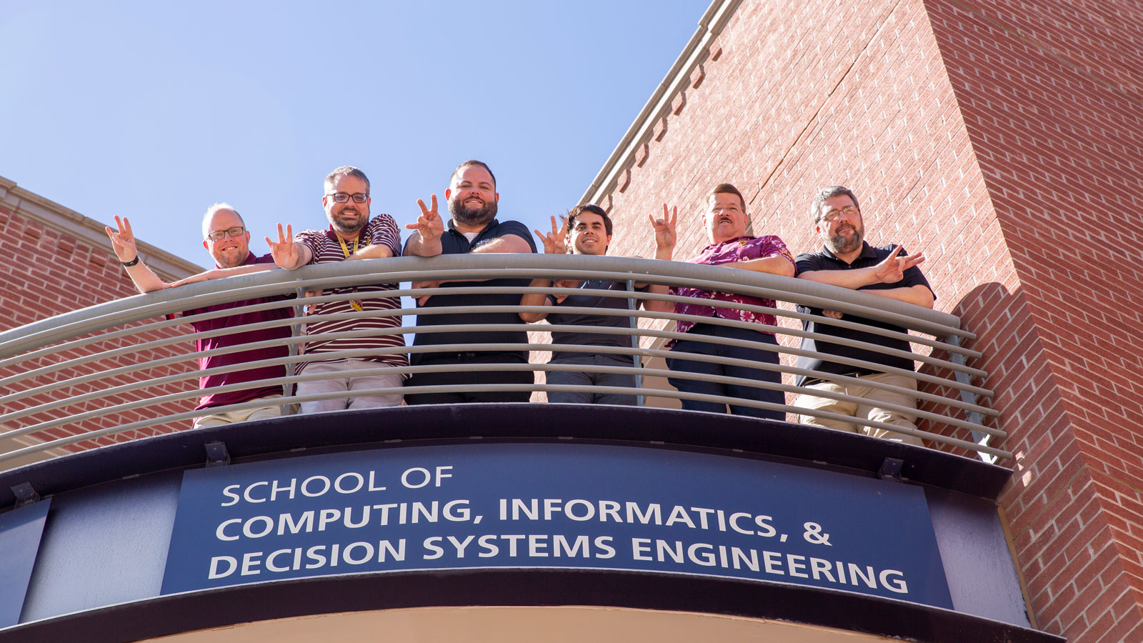 School of Computing, Informatics, and Decision Systems Engineering information technology team poses on a balcony.