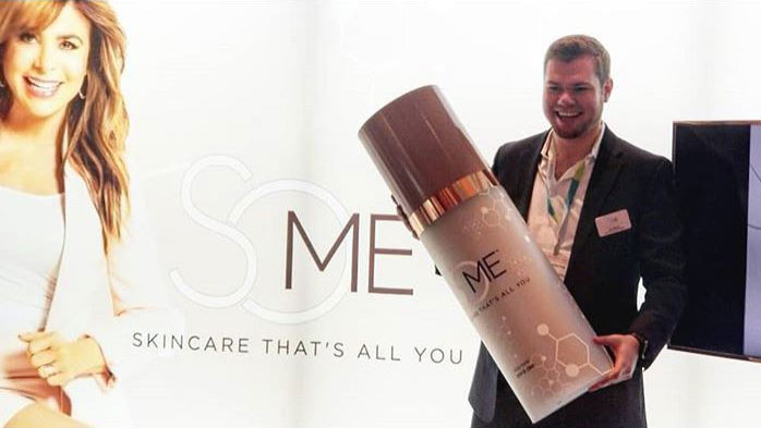 man holding an oversized skincare product