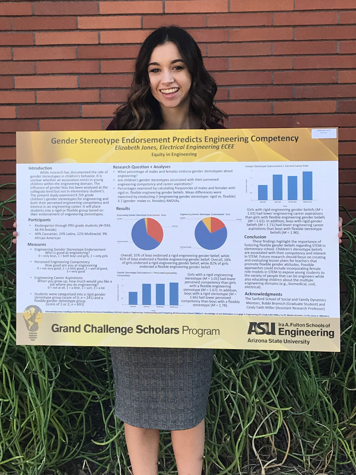 Elizabeth Jones holds a Grand Challenges Scholars Program poster that details her project about gender stereotypes affecting engineering competency in elementary school students.