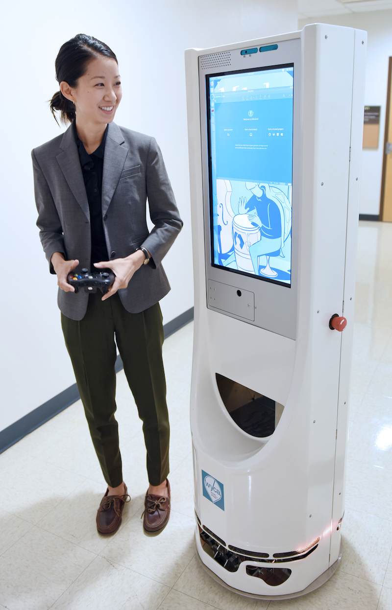 Erin Chiou standing next to a mobile robot