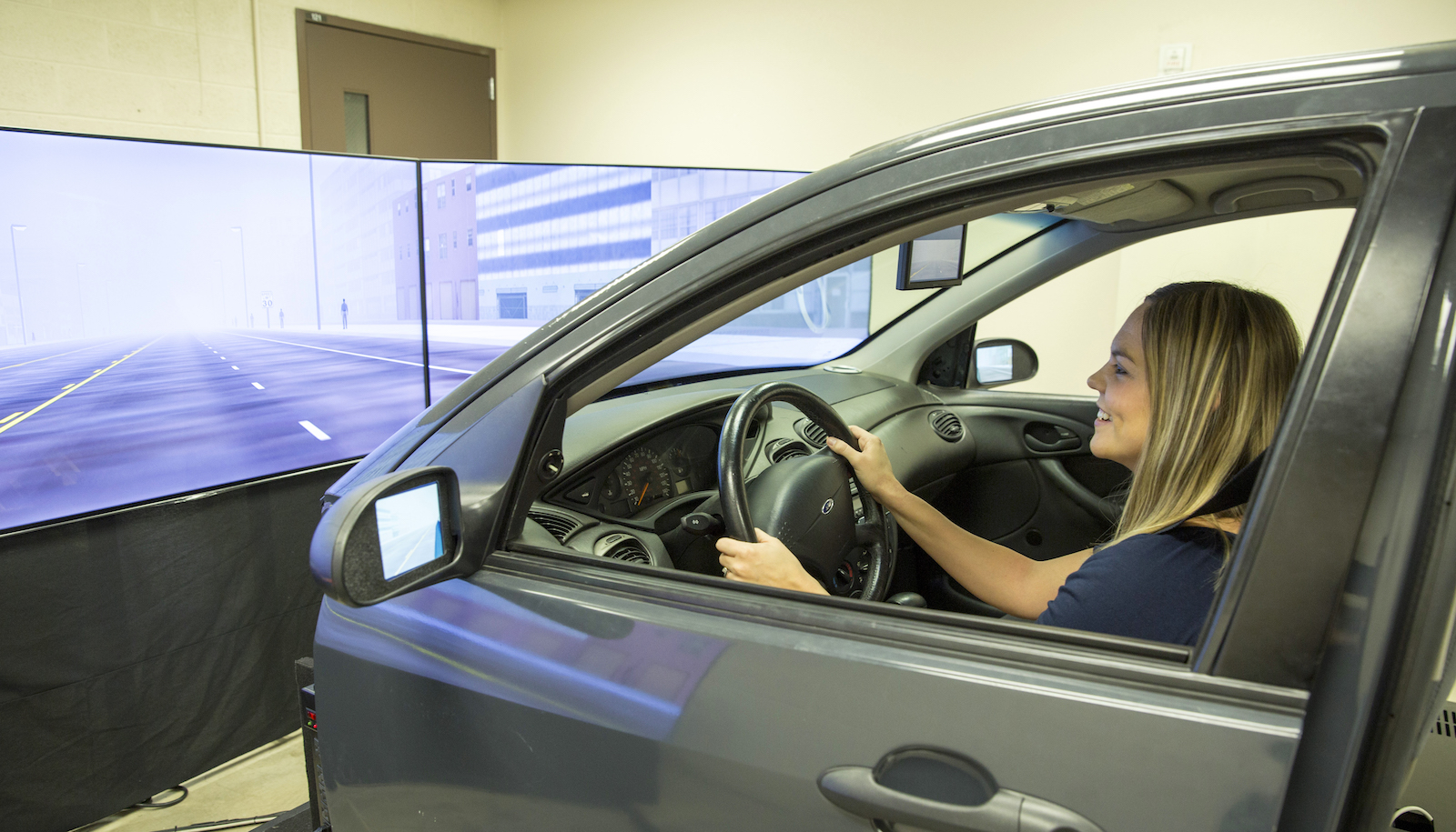 image of woman in a car as part of a driving simulator