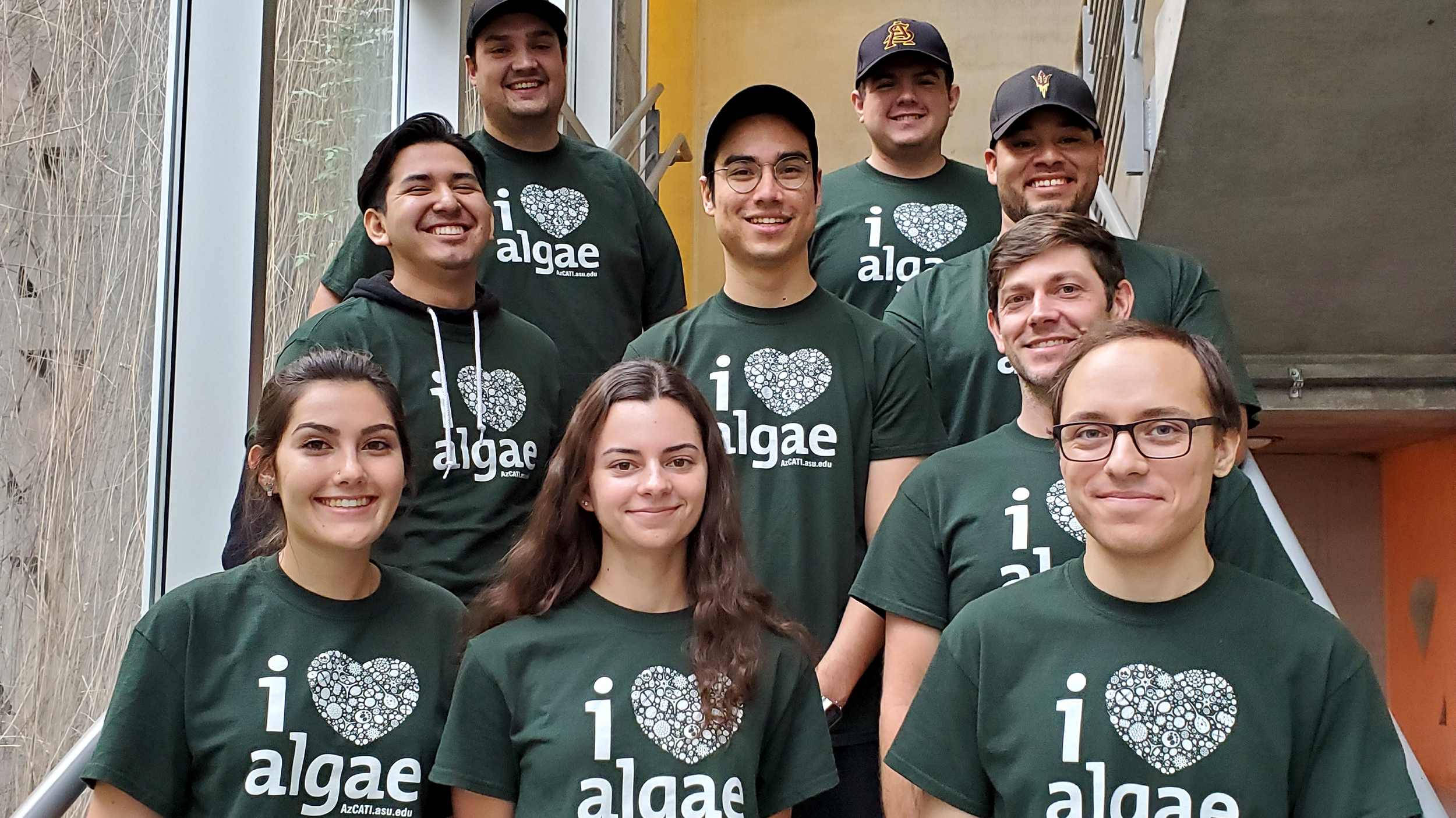 "nine students in matching shirts the say ""I heart algae"" posing on stairs"