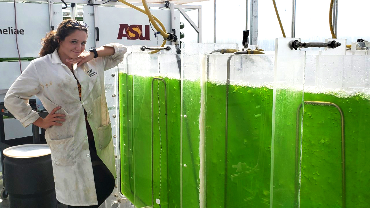 woman standing next to algae containers