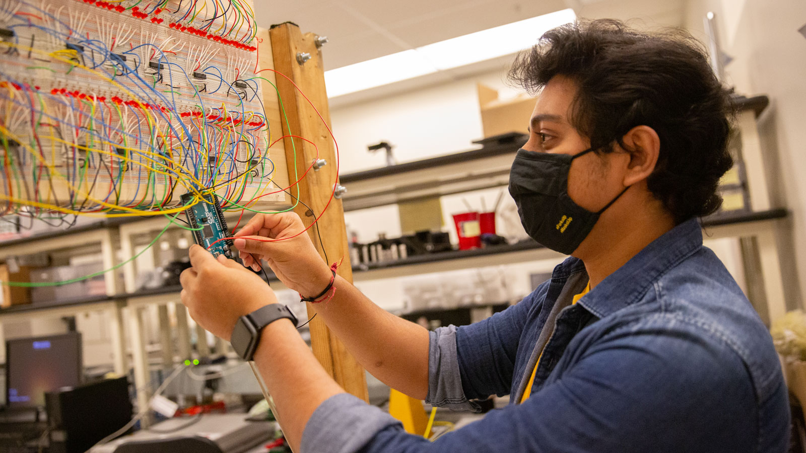 Anand Sengar examines small, colorful wires in a lab.