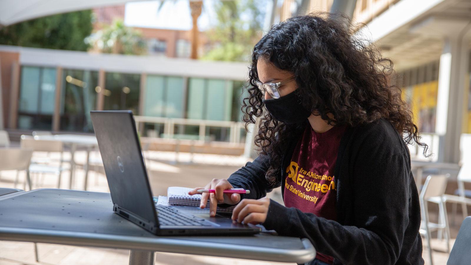 Sabrina Cervantes Villa works on a laptop outside.