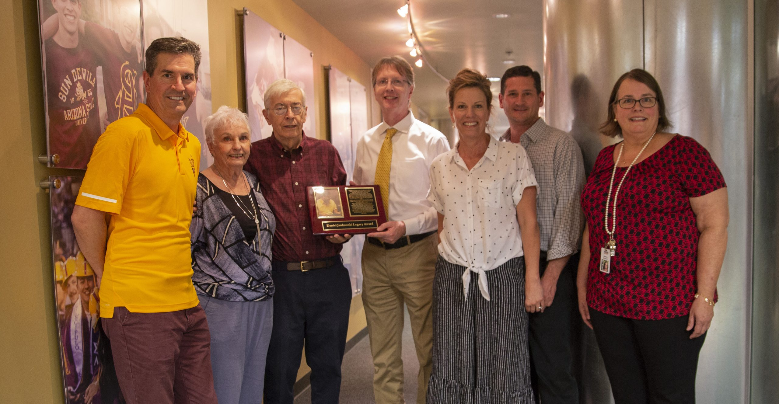 Photo of seven people in a hallway posing with a Jankowski Legacy Award plaque