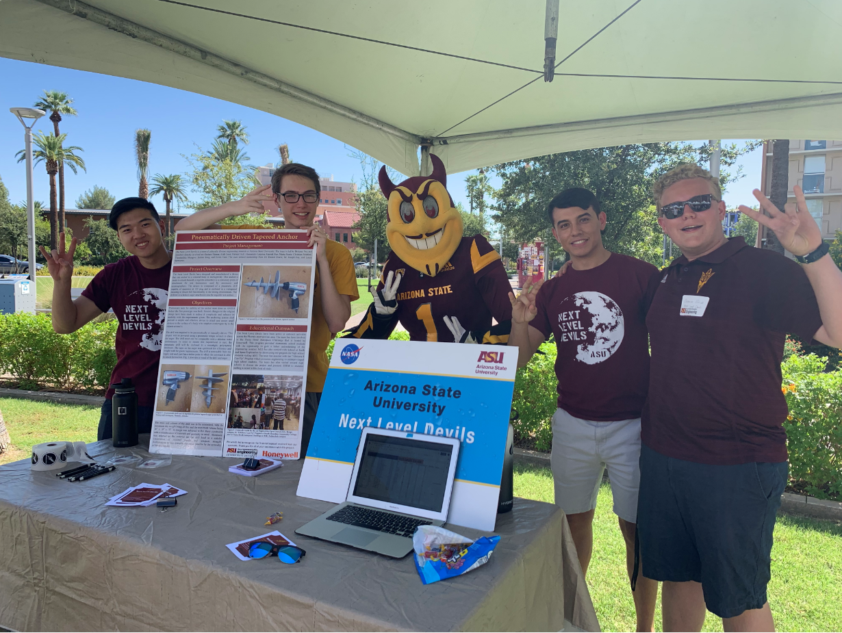 Four students from the Next Level Devils student team pose at an event with Sparky the Sun Devil