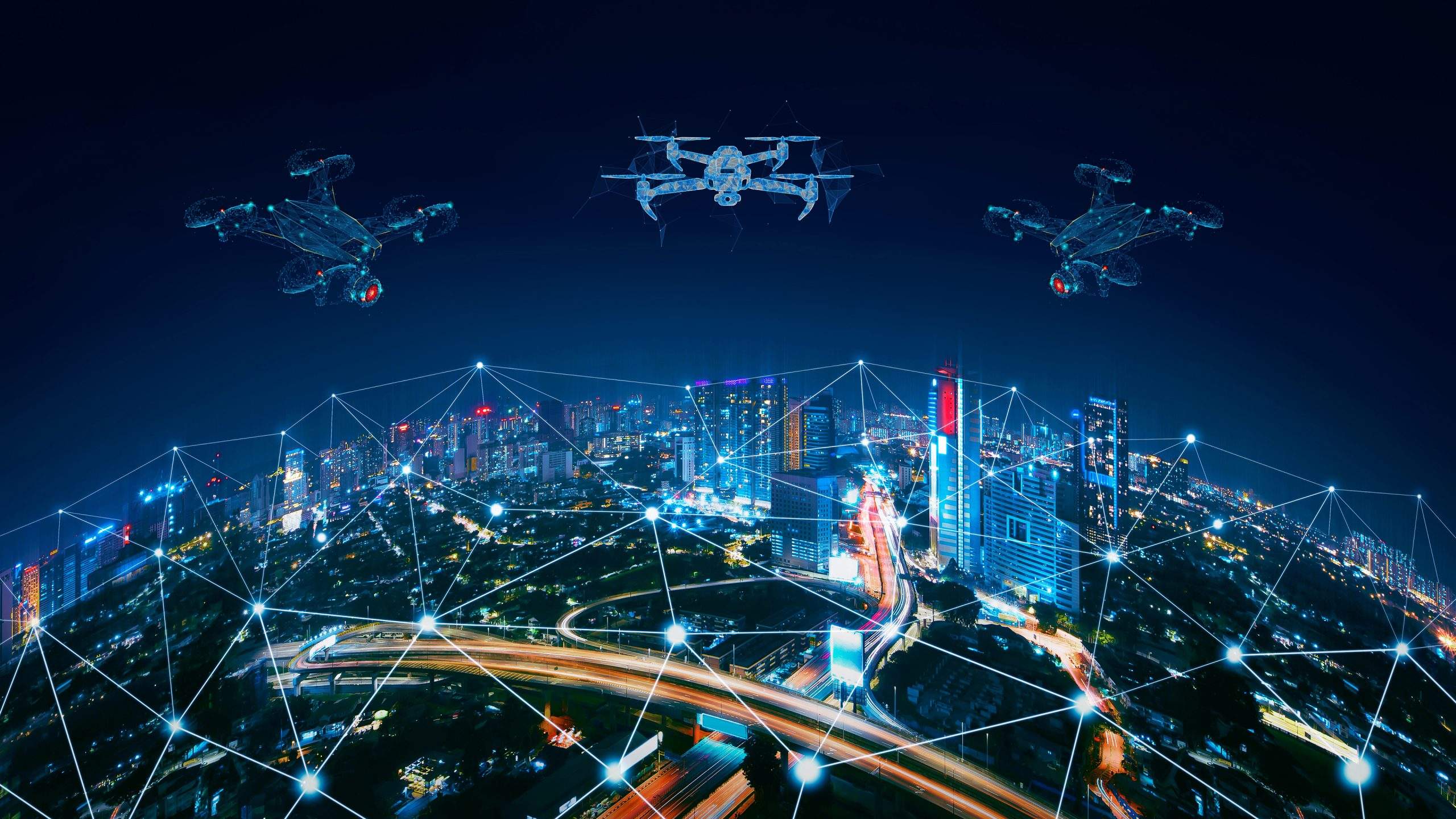 Birdseye view of a city lit up at night with UAVs hovering over connecting wireless points