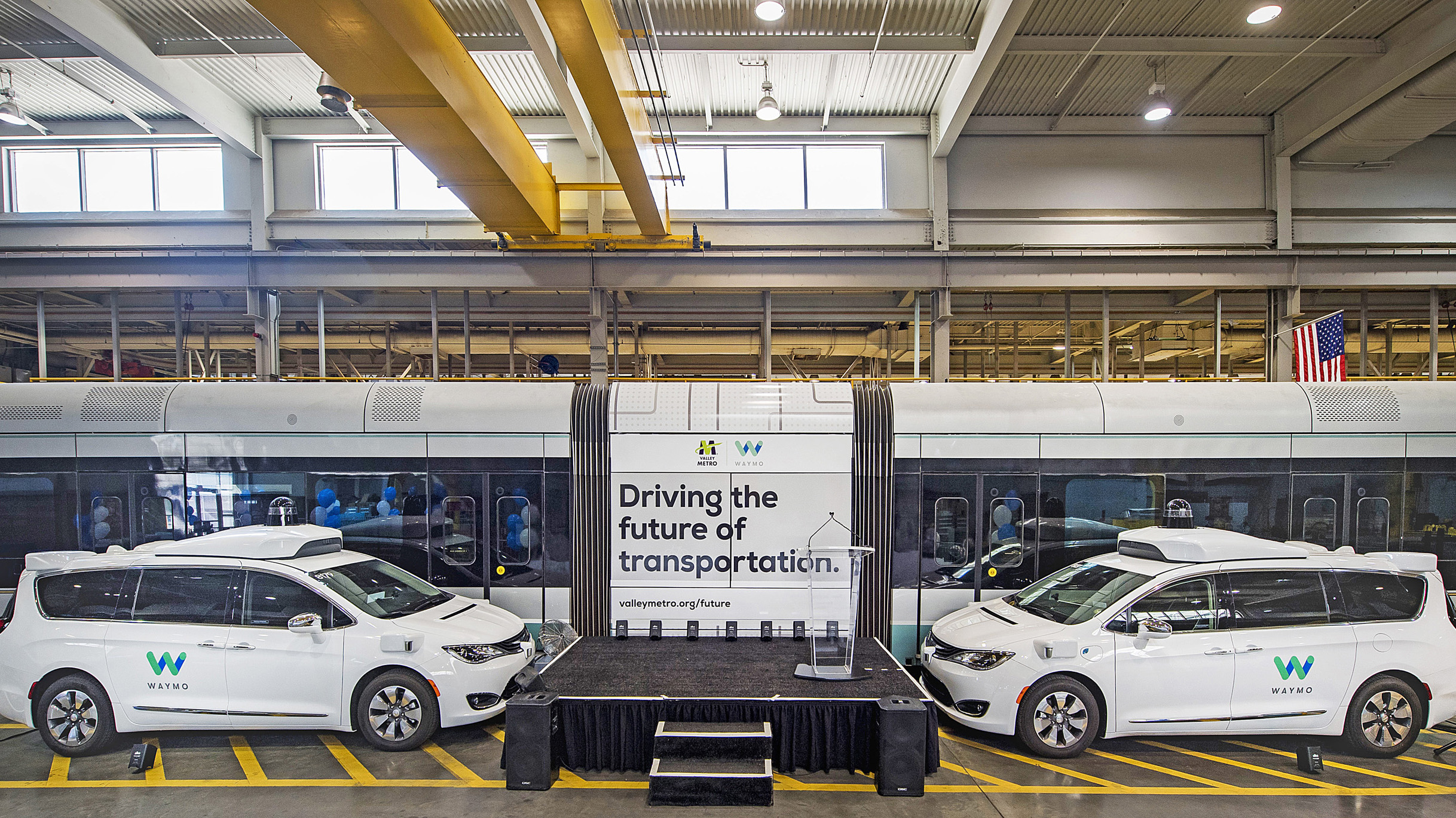 Pair of Waymo autonomous vehicles next to a stage