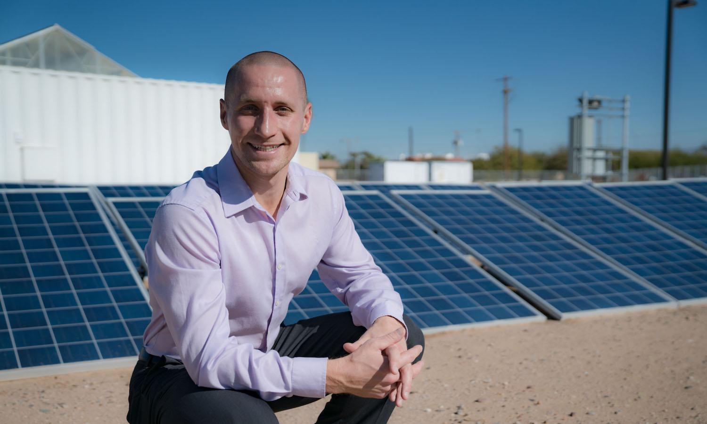 Photo of Nathan Johnson next to solar panels