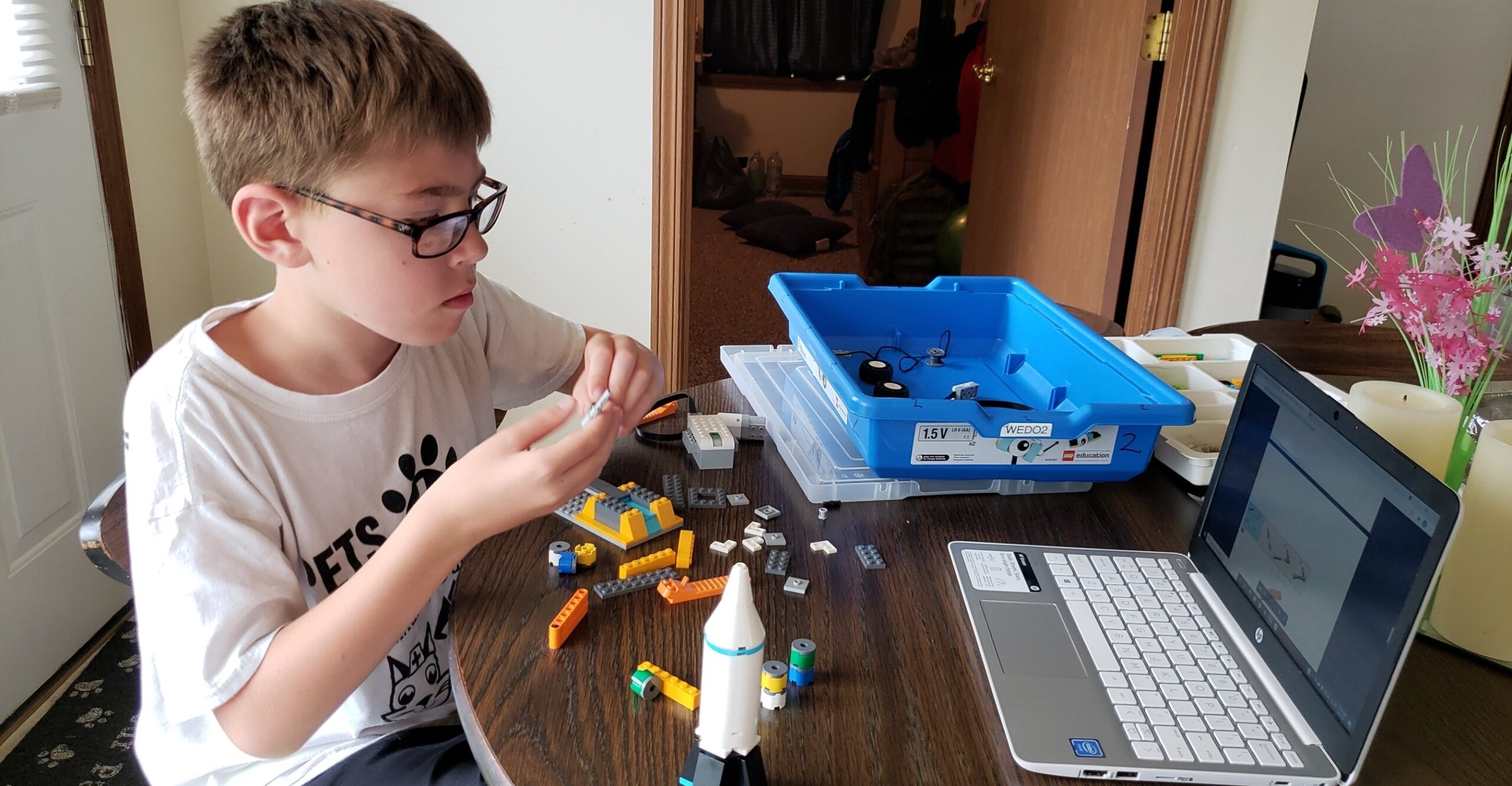 student buliding a LEGO robot project during a virtual summer camp